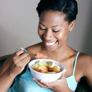 Woman Eating Fruit Salad & Laughing